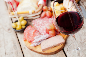 Glass of red wine with charcuterie assortment on the background