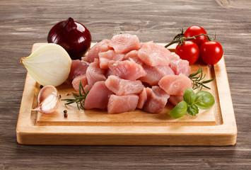 Raw turkey meat on cutting board on wooden background