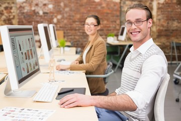Smiling photo editors using computers in office