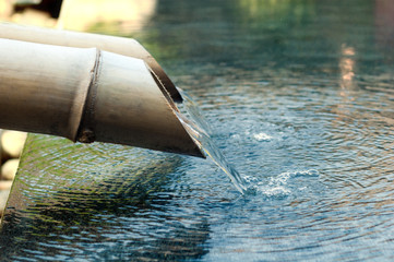 water falling down from bamboo pipe