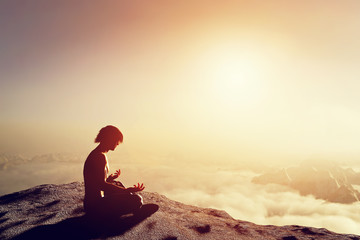 Asian man meditates in yoga position in high mountains at sunset