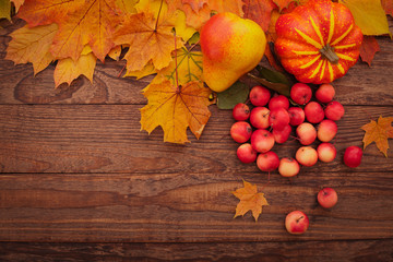 Autumn leaves on wooden table. Fruits and vegetables.