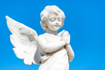 Beautiful infant angel on a blue sky