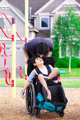 Disabled boy in wheelchair with big brother at park
