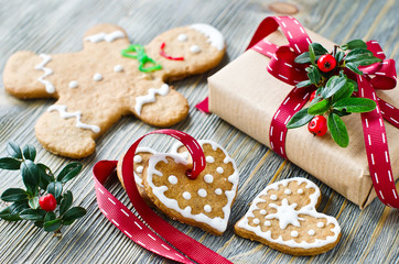 Christmas gift box and gingerbread cookies on wooden background