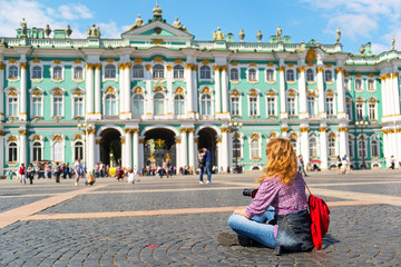 Fotomurales - Young female tourist in front of the Winter Palace in St. Peters
