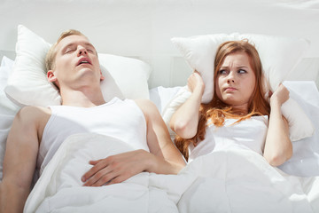 Woman being angry on snoring boyfriend