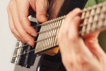 Hands of guitarist playing the electric bass guitar closeup