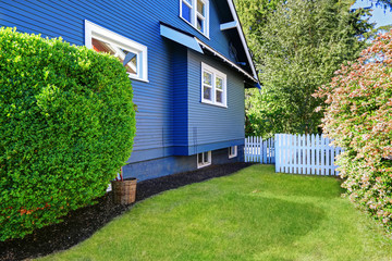 Backyard with lawn and white wooden fence