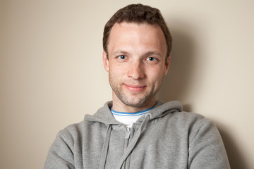 Young smiling Caucasian man in gray sports jacket with hood