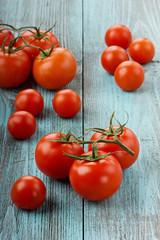 Red tomatoes on a turquoise colored wooden surface