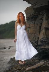 Beautiful redhead woman in white dress goes along the coast.