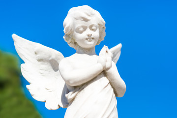 Beautiful infant angel on a blue sky background