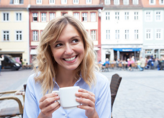 Frau mit blonden Locken träumt im Strassencafe