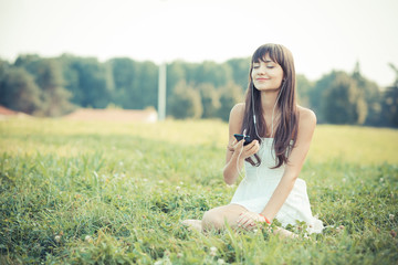 beautiful young woman with white dress listening music