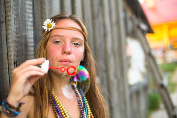 Hippie girl blows soap bubbles on a street .