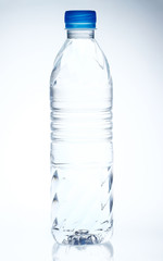 Plastic bottle of drinking water on white