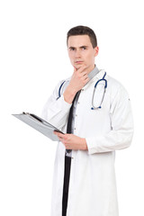 Thinking young male doctor holding a clipboard