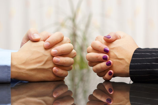 Man and woman sits at a desk with hands clasped. marital problem
