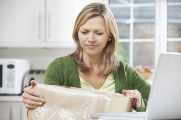 Disappointed Woman Unpacking Online Purchase At Home