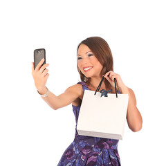 Beautiful girl holding shopping bags and taking selfie