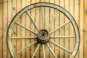 Vintage wagon wheel in front of a barn