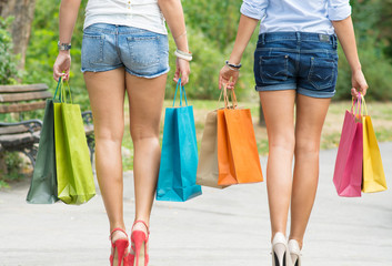 backs of young friends carrying shopping bags