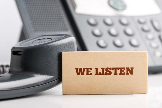 Rectangle saying We listen on white telephone desk