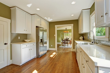 Green kitchen room with white storage combination