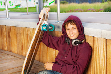 Boy wears hood and holds skateboard while sitting
