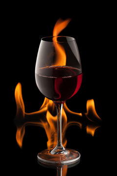 glass of wine on black background with fire splash