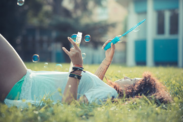 young beautiful moroccan curly woman blowing bubbles