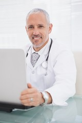 Smiling doctor using laptop