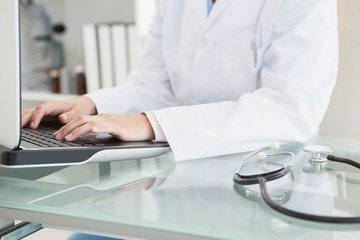Doctor typing on her laptop