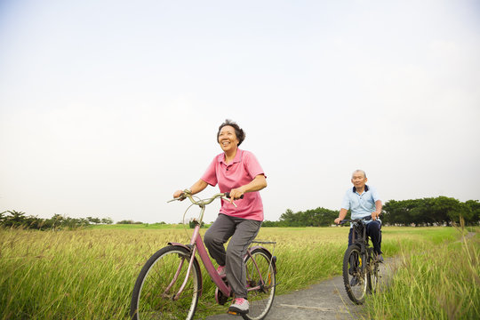 Happy Asian elderly seniors couple biking in the park with blue