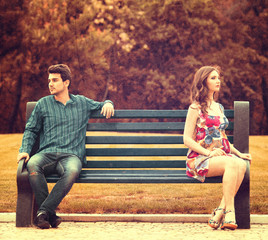 Young couple sitting apart on the bench in the park
