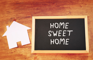 top view of blackboard with the phrase home sweet home and house