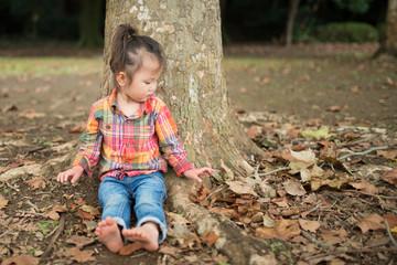 木に寄りかかる少女