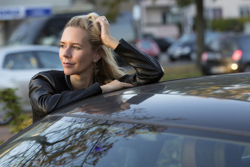 blond woman standing by a car