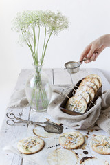 homemade cookies on white wooden table with wildflowers
