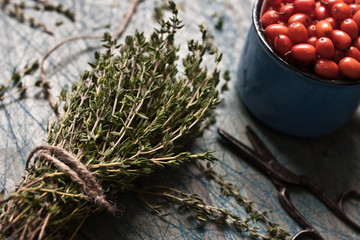 Thyme bunch with a cord and a cup with sea-buckthorn