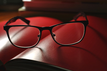 black glasses and red book
