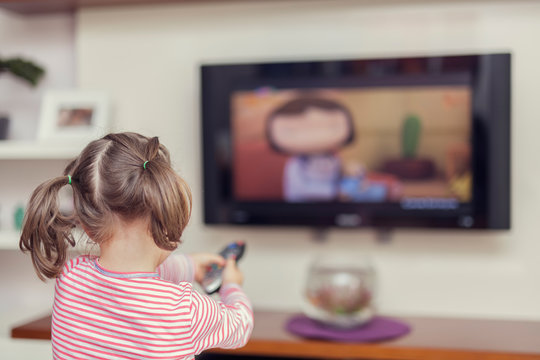 little cute girl with remote changes channel on tv
