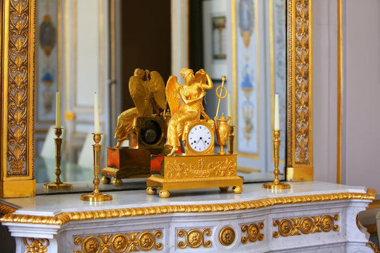 Antique clock with figurine of angel in vintage interior.