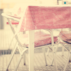 Outdoors table in a cafe with checkered vintage tablecloth