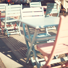 Vintage pink and turquoise tables and chairs in a sidewalk cafe
