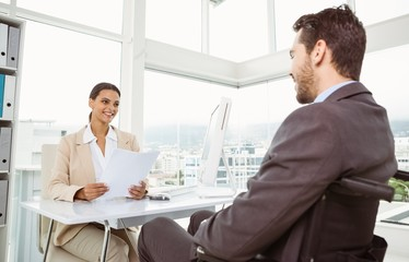Businesswoman interviewing man in office