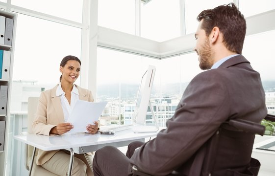 Businesswoman interviewing man in office