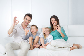positive family sitting on sofa