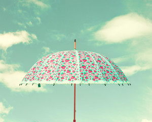 Vintage colorful umbrella and sky with clouds